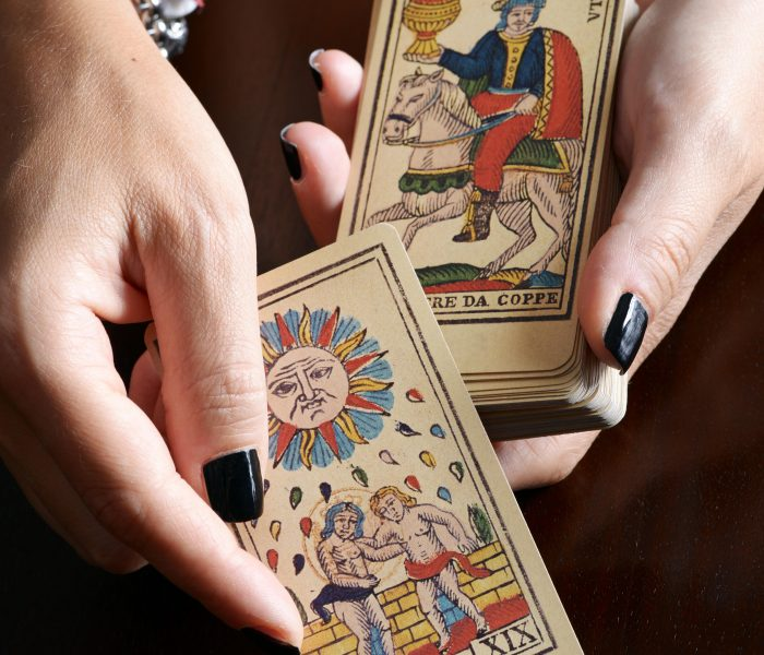 HGXH23 Close up view female hands with black nail art and bracelet showing old tarot card and card deck over dark table